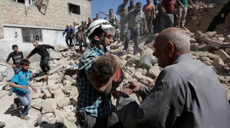 A civil defence member carries the body of a dead child at a site hit by airstrike in the rebel-controlled area of Maaret al-Numan town in Idlib province